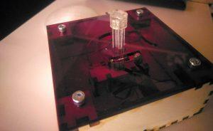 Ein Bild des zusammengebauten Quizbuzzers, ohne den Schirm des Schalters. Die Buchsen, an denen die LEDs angesteckt werden können, sowie der Stamm des Schalters, ragen durch den Deckel.